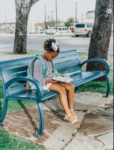 Girl reading on a bench outside the library