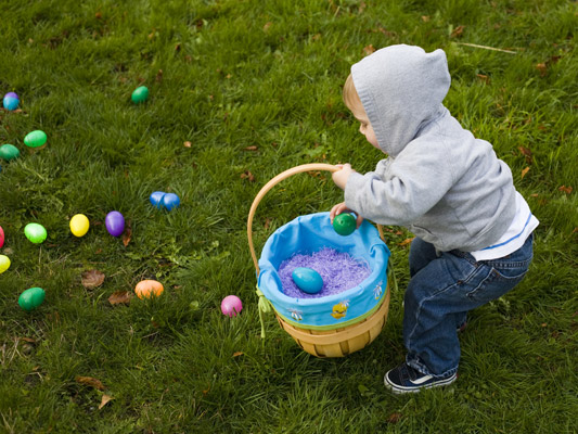 Child with an Easter basket is picking up Easter eggs from off the ground.